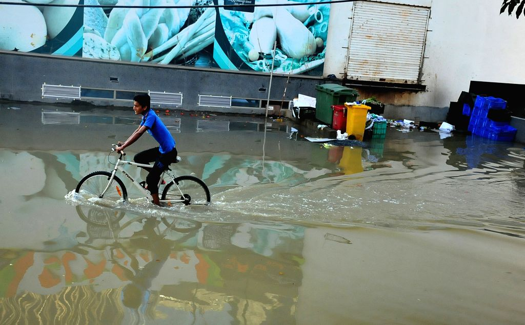 A boy cycles through the flooded streets after rains lashed in Bengaluru on Sept 10, 2017.