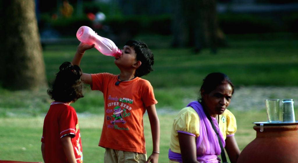 A boy drinks water to beat the heat on a hot day in New Delhi on June 3, 2016.