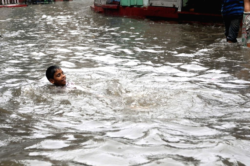 A boy enjoys in water collected during rains, in Kolkata on July 26, 2018.
