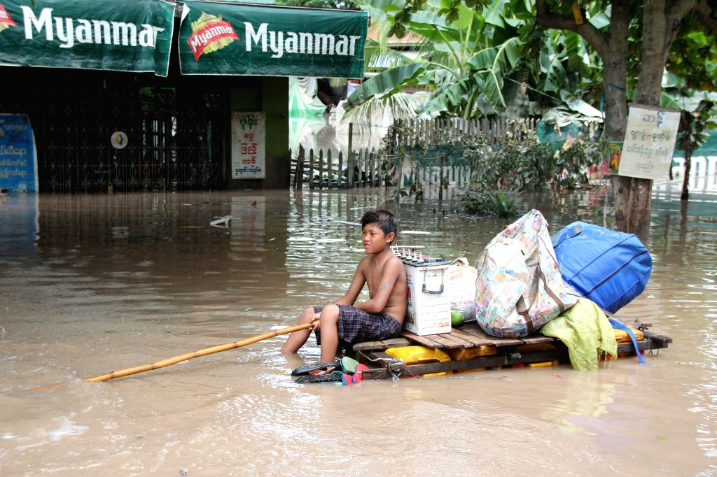 A boy on a makeshift raft paddles his way through a flooded area in Kalay township of Sagaing Region, Myanmar, Aug. 3, 2015. Heavy monsoon rains have left at least 47 ...