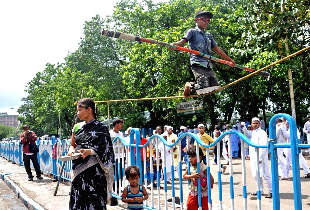 A boy performs a balancing acts on the rope and entertain the crowds on the occasion of Eid-ul-Fitr in Kolkata on June 26, 2017.