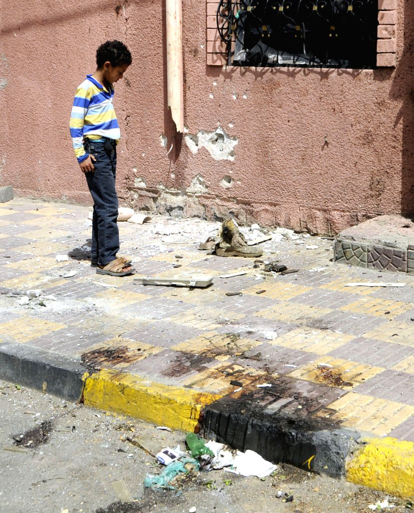 A boy stands at the blast site outside the Saba news agency in Sanaa, Yemen, on June 25, 2015. An explosive device went off outside Yemen's state-run Saba news agency ...