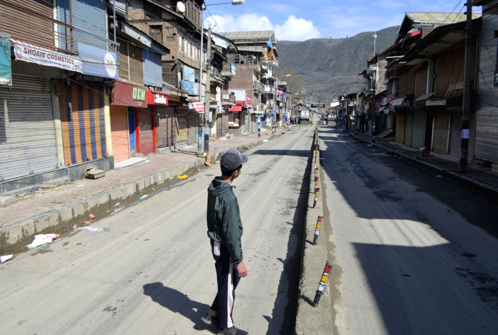 A boy stands in the midst of a deserted street surrounded by closed shops as complete shutdown is being observes across Jammu and Kashmir during a nationwide shutdown - Janata Curfew - ...