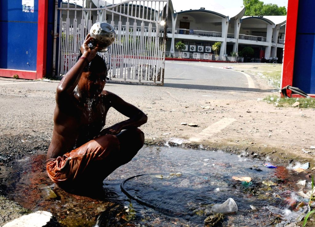 A boy takes a bath at a street side on a hot sunny day in Patna, on April 15, 2019.