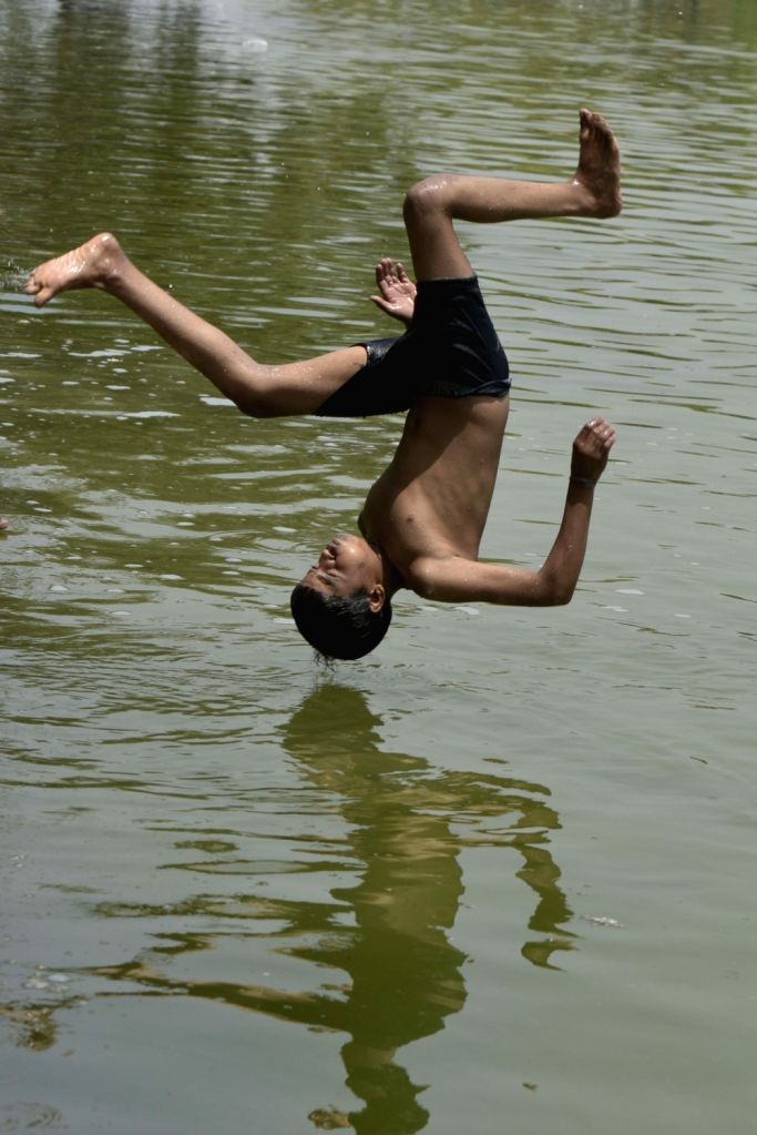 A boy takes a plunge into a pond to beat the heat on a hot summer day, near India Gate in New Delhi, on June 4, 2019.