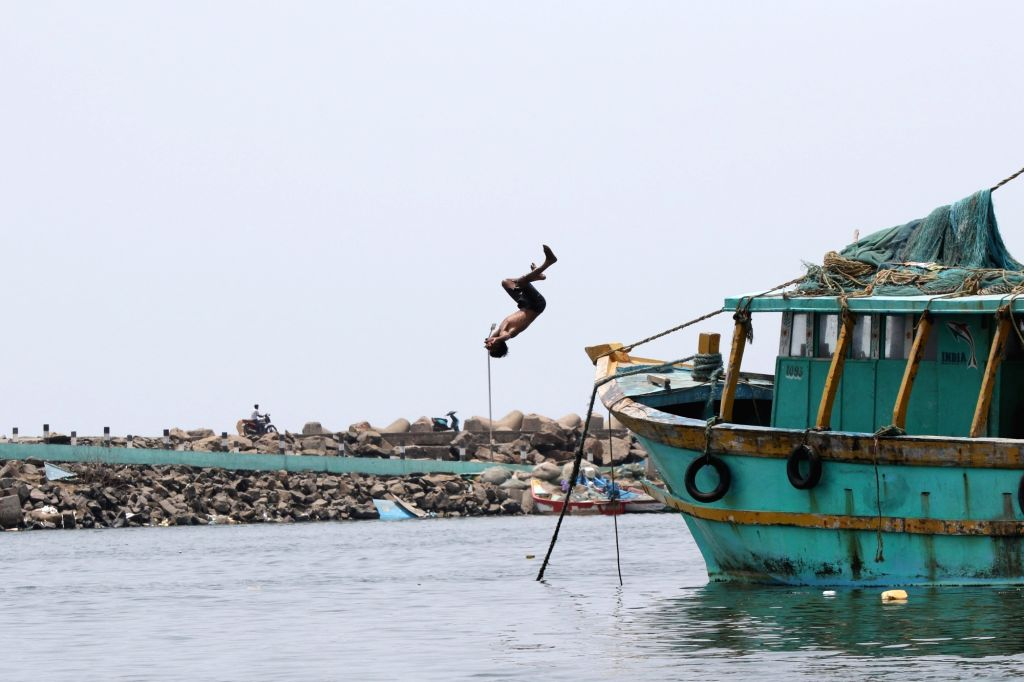A boy takes a plunge into the water at Kasimedu fishing harbour to get respite from the heat on a hot sunny day, in Chennai on May 21, 2018.