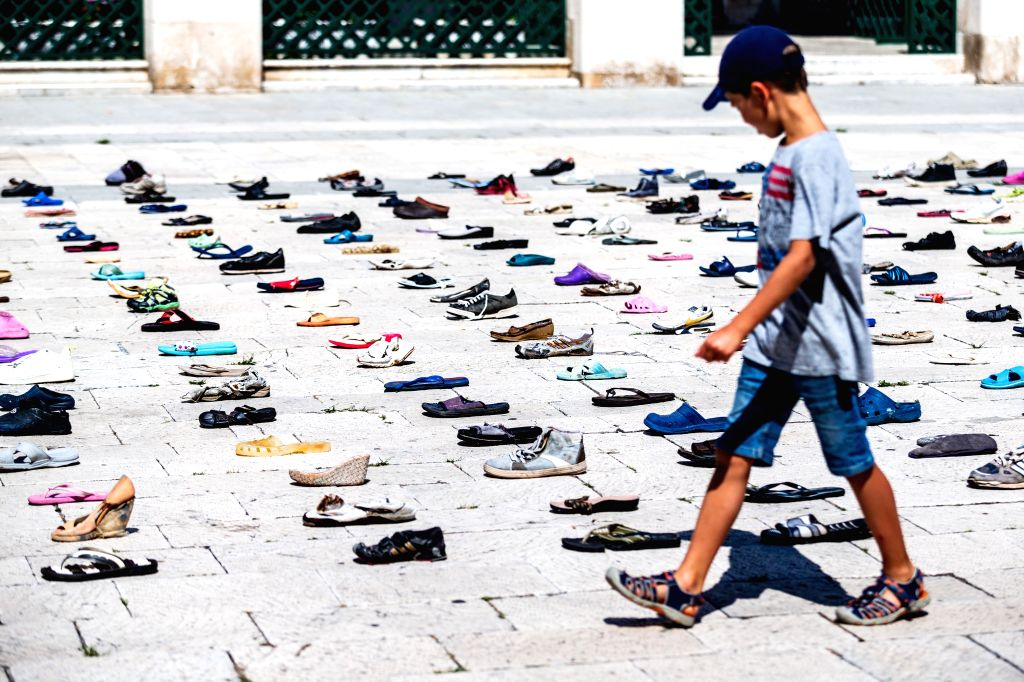 "A boy views the art installation ""1000 Cinderellas"", which consists of 1,000 shoes laid out by artist Mark Boellaard, on Prokurative Square in Split, ... - Mark Boellaard"
