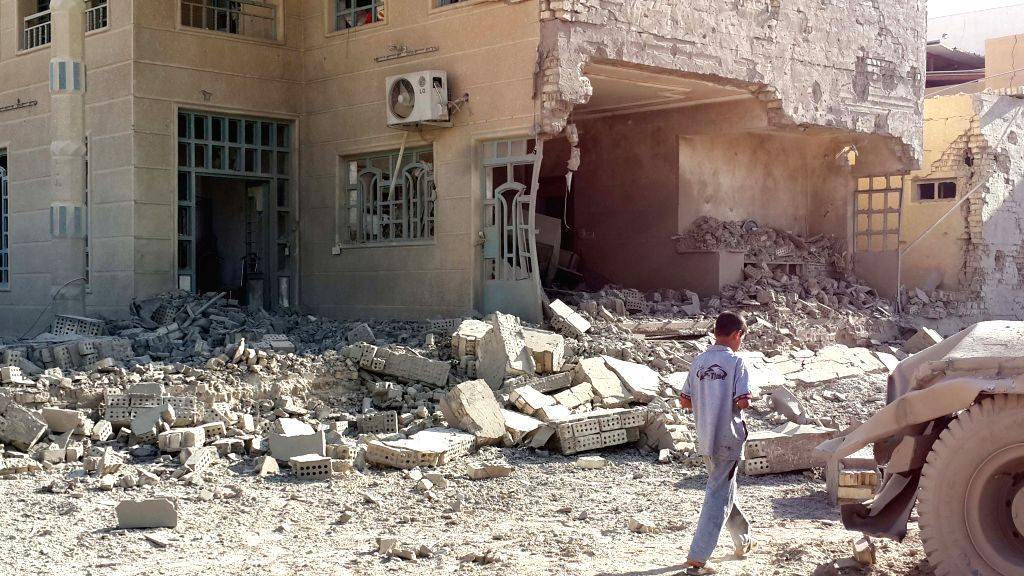 A boy walks past a destroyed building after an airstrike by the Iraqi Air Force in Islamic State (IS) militants-seized city of Fallujah, some 50 kilometers west of ...