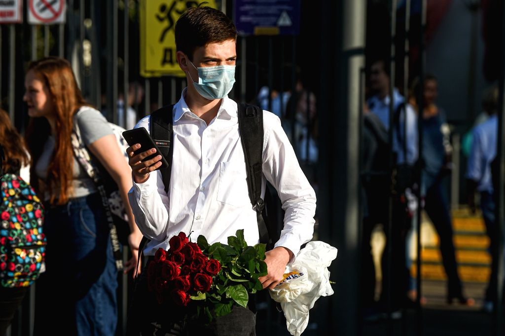 A boy wearing a face mask stands by the school entrance on the first day of school in Moscow, Russia, on Sept. 1, 2020. Russia registered 4,729 new COVID-19 cases in ...