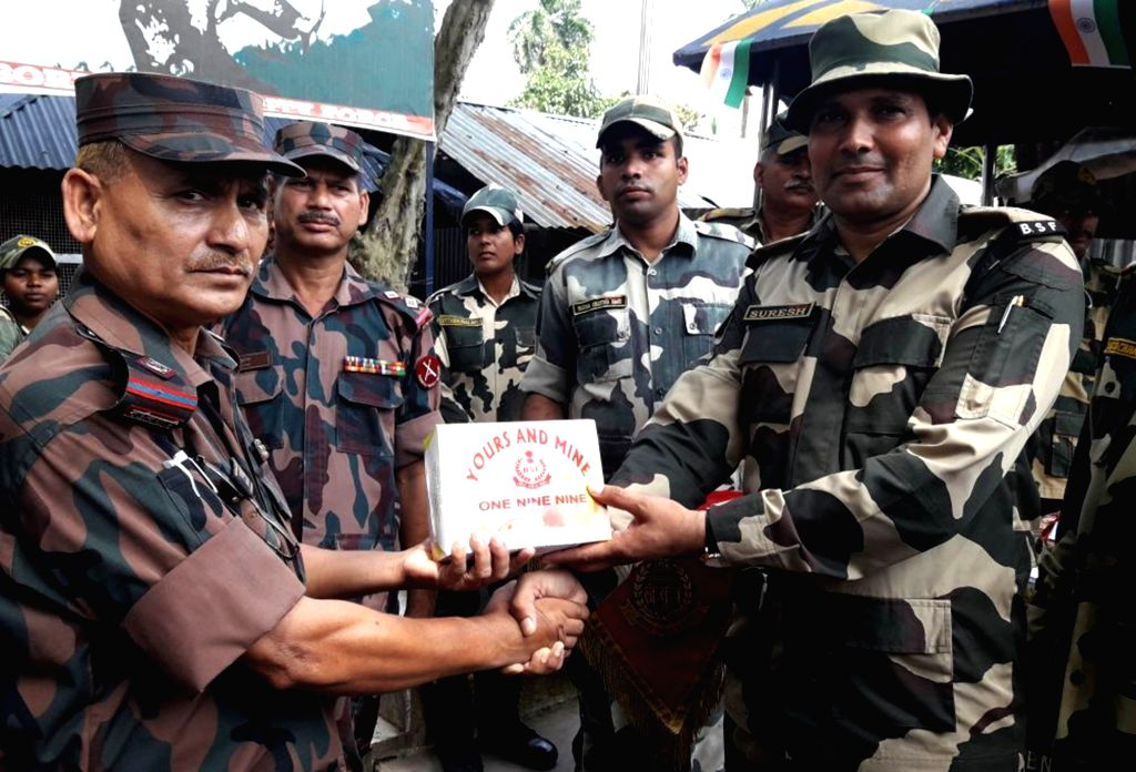 A BSF officer presents sweets to BGB personnel during India's Independence Day celebrations at the International Immigration check-post at Hili in South Dinajpur district of West Bengal on Aug ...