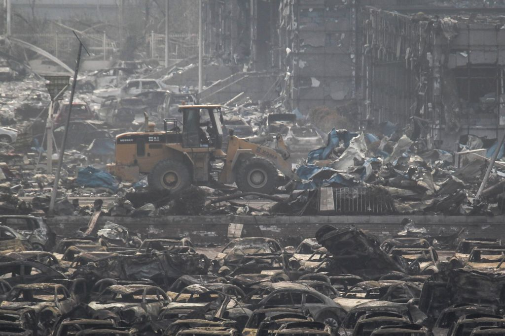 A bulldozer clears off wreckage at the warehouse explostion site in Tianjin, north China, Aug. 17, 2015. Death toll of the massive Tianjin blasts rose to 114 after ...