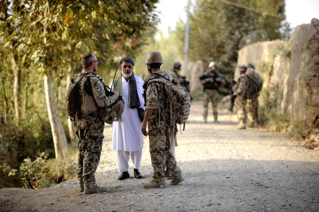 A Bundeswehr soldier (L) and an interpreter (R) speak to a man near Afghanistan's Kunduz in the Chahar Dara district. Photo: Maurizio Gambarini/dpa/IANS
