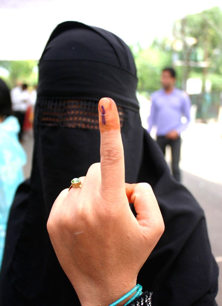 A burqa clad woman shows her fore finger marked with phosphoric ink after casting her vote during the fifth phase of 2014 Lok Sabha Polls in Bhopal on April 17, 2014. Elections are being held in 117 .