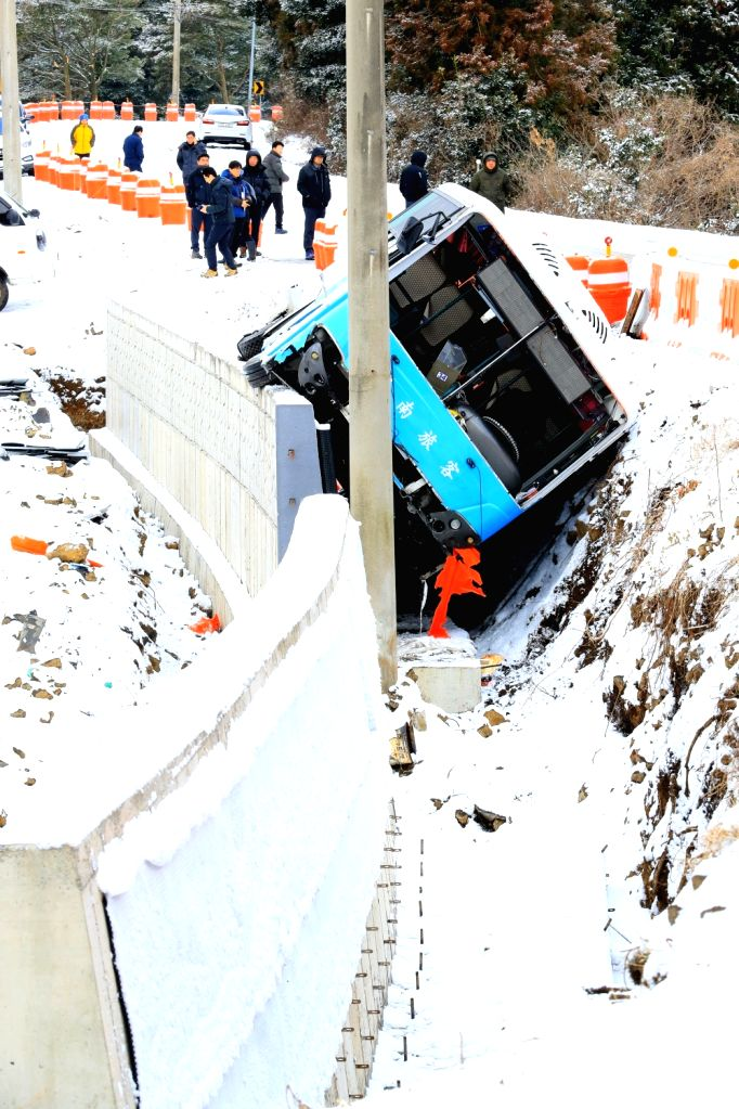 A bus is stuck between a concrete wall and a snow-covered road in the city of Jeju on South Korea's island of the same name on Jan. 30, 2018, after skidding off the road. The accident, which ...