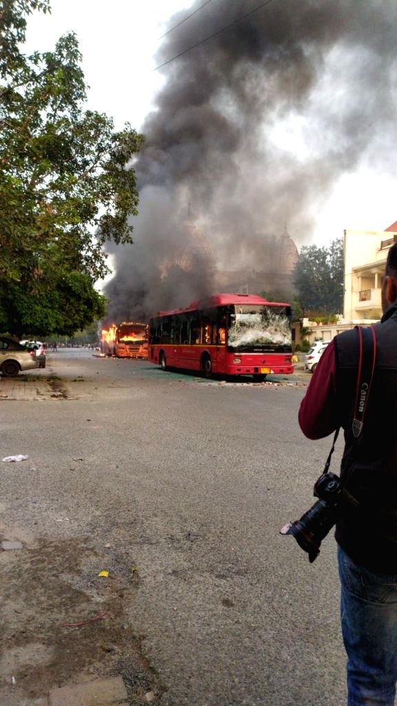 A bus set ablaze after a scuffle that broke out between the Delhi Police and Students of Jamia Millia Islamia in New Delhi on Dec 15, 2019.