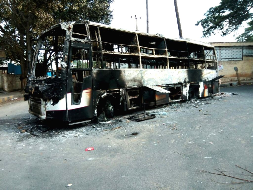 A bus with Tamil Nadu registration number that was torched by protesters on Bengaluru-Mysuru road on Sept 13, 2016. Uneasy calm prevailed in the city where one person was killed in police ...