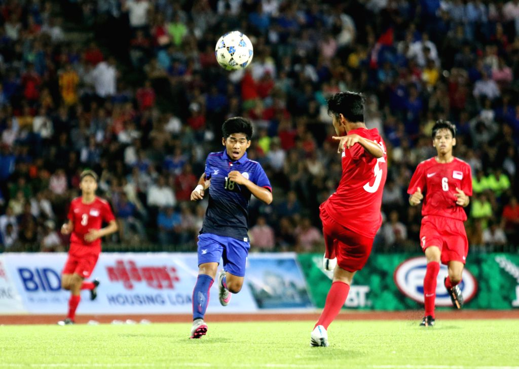 A Cambodian U16 player (blue uniform) and Singaporean players (red uniform) vie for the ball during a match in Phnom Penh, Cambodia, Aug. 3, 2015. The host ...
