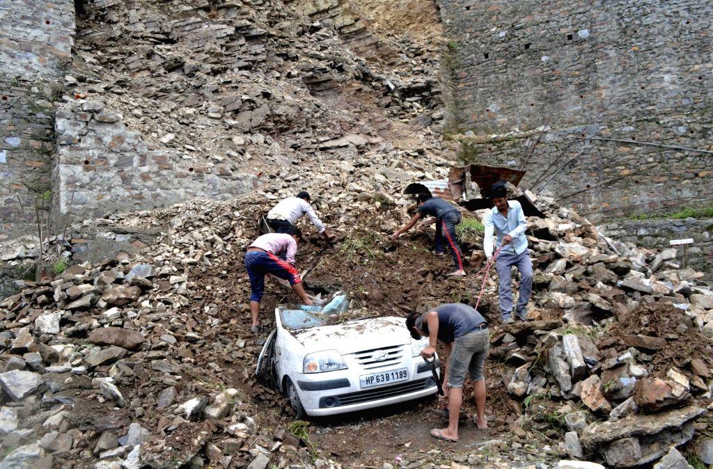 A car damaged during landslide in Shimla on July, 2018.