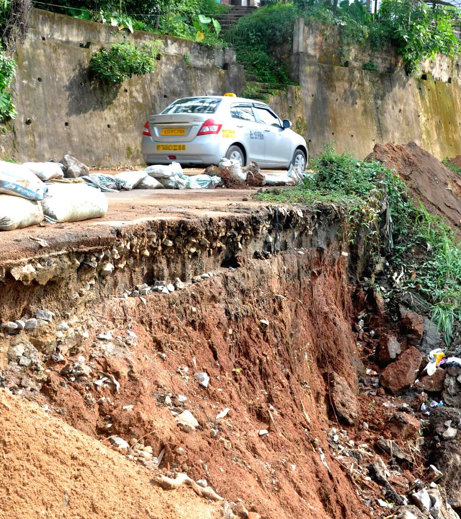 A car moves cautiously as it travels on a road a portion of which got destroyed in a landslide in Guwahati on July 8, 2014.