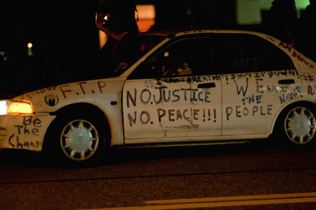 A car painted with slogans is seen during a manifestation in Ferguson, the United States, on Aug. 11, 2015. Protests marking the anniversary of the shooting of ...