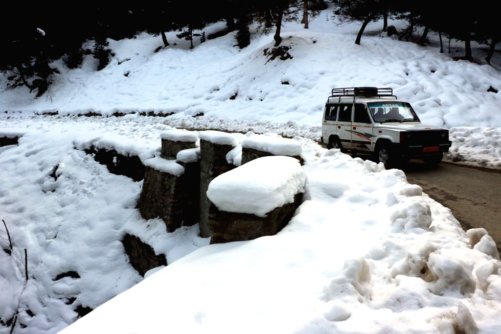 A car runs on Gulmarg-Srinagar road after snowfalls in Gulmarg on Jan 19, 2016.