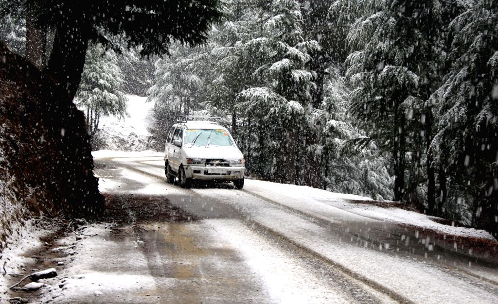 A car runs on snow covered roads in Baramulla district of Jammu and Kashmir on March 11, 2017.