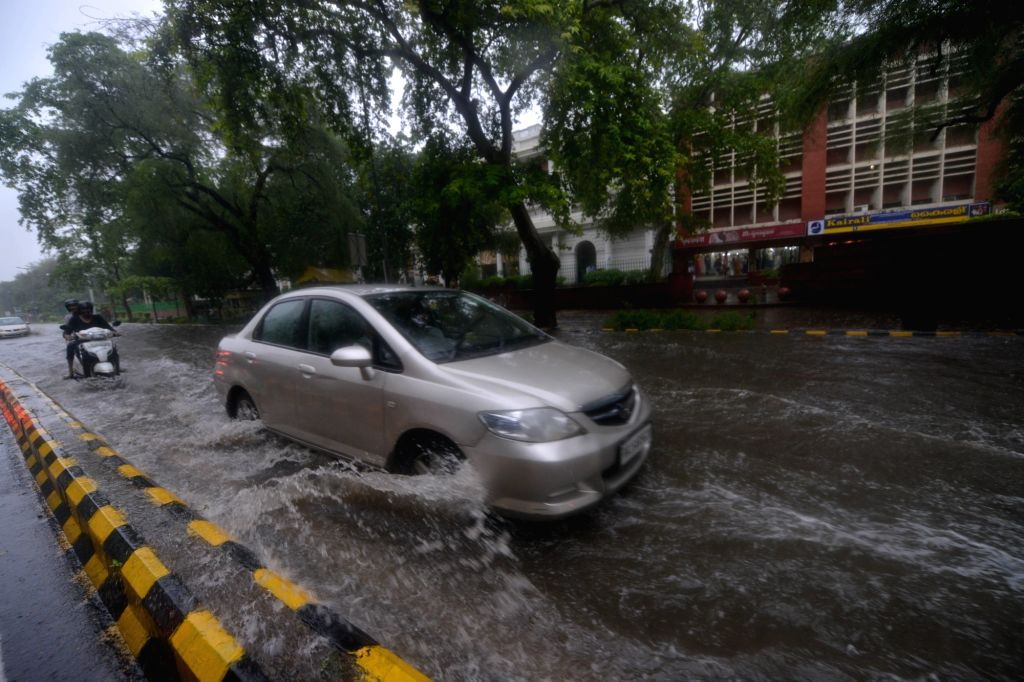 A car struggles through a water logged road in Connaught Place of New Delhi on July 13, 2018.