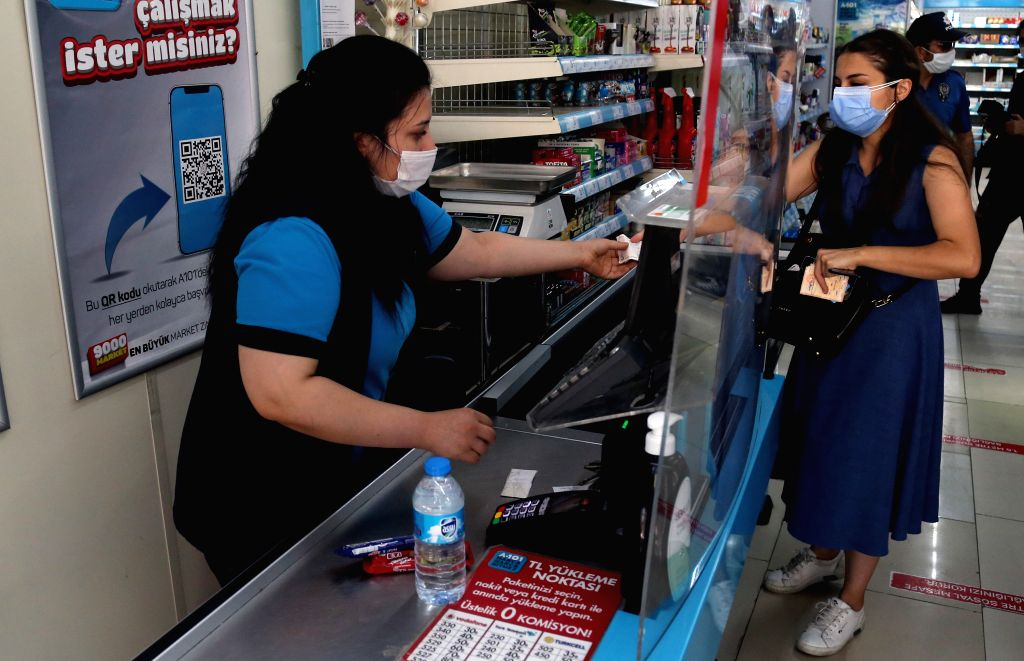 A cashier checks out a customer's items at a supermarket in Ankara, Turkey, on Aug. 11, 2020. Turkey confirmed 1,183 new COVID-19 cases on Tuesday, raising the total ... - Fahrettin Koca