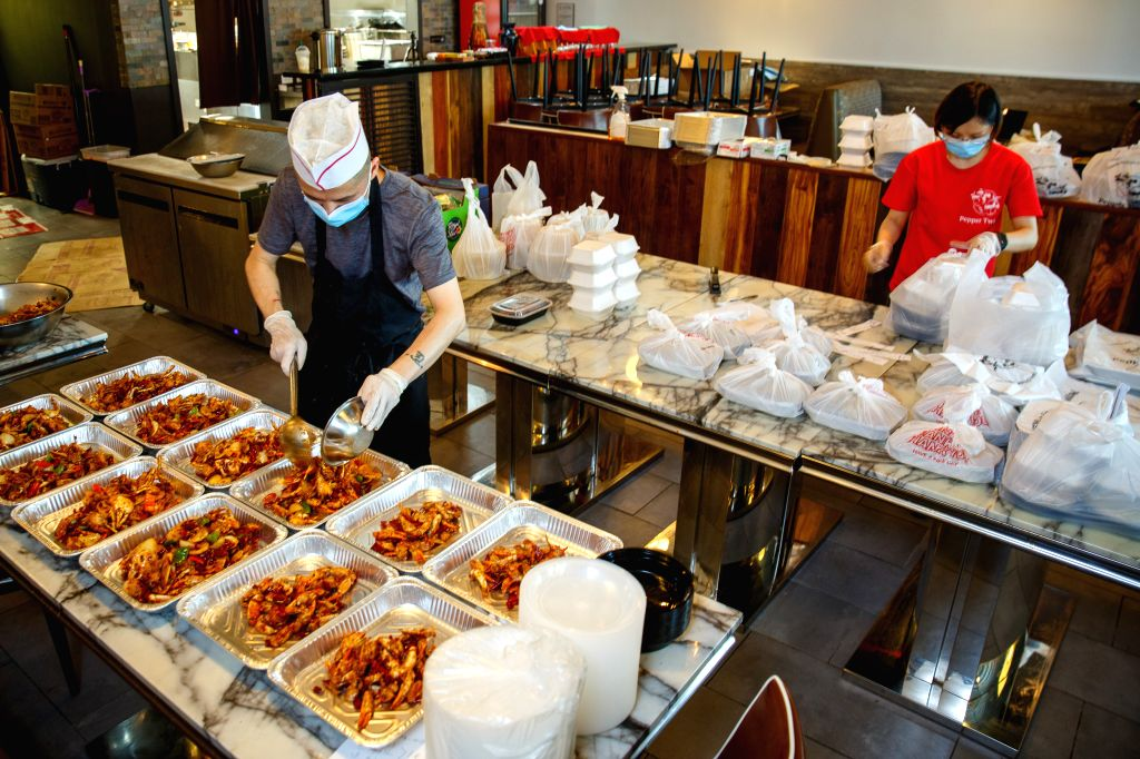 A chef wearing a face mask works at a Chinese restaurant in Houston, Texas, the United States, on July 2, 2020. U.S. state of Texas added more than 7,500 new ...