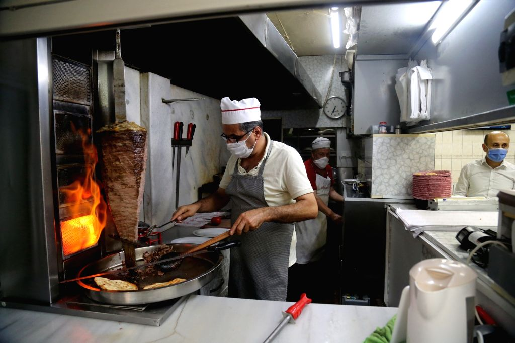 A chef wearing a mask works at a restaurant in Ankara, Turkey, on Sept. 11, 2020. Turkey confirmed 1,671 new COVID-19 cases on Friday, raising the total diagnosed ...