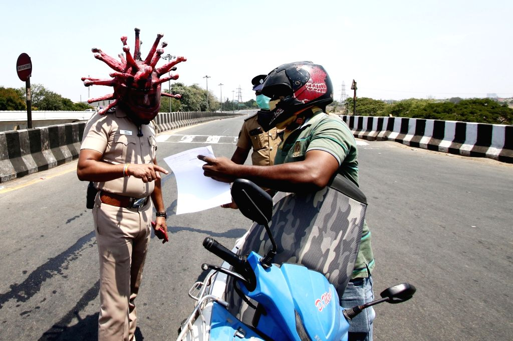 A Chennai cop wearing a 'Corona Helmet' intercepts a lockdown violater on March 29, 2020. The cop wearing the helmet, police Inspector Rajesh Babu in collaboration with a local artist ... - Gowtham and Narendra Modi