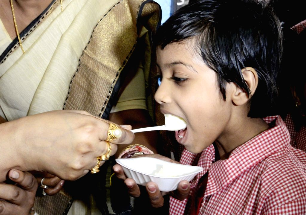 A child being fetched a Rosogolla - an Indian ball-shaped syrupy sweet - during 'Rosogulla Day' being observed across West Bengal on the occasion of Children's Day, in Kolkata on Nov 14, ...