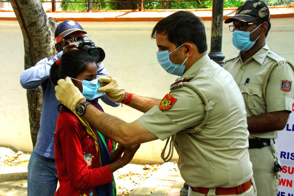 A child being made to wear a mask by a police personnel during the distribution of burgers among children from different clusters of South Delhi as part of the Delhi Police's initiative to ...