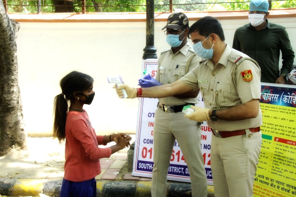 A child being screened for COVID-19 during the distribution of burgers among children from different clusters of South Delhi as part of the Delhi Police's initiative to to bring smiles on ...