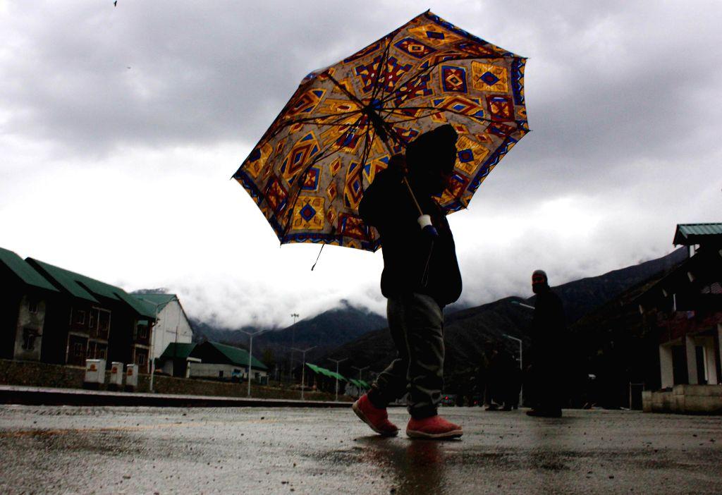 A child carries an umbrella as it rains in Srinagar on April 18, 2014.