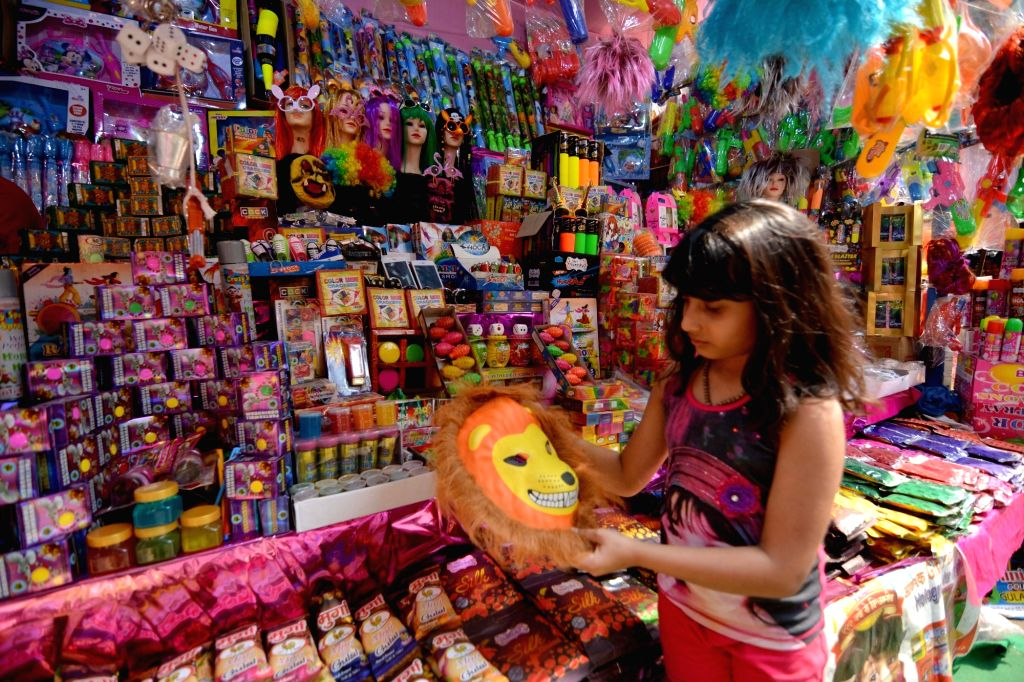 A child checks out a mask at a shop ahead of Holi in Kolkata, on March 14, 2019.