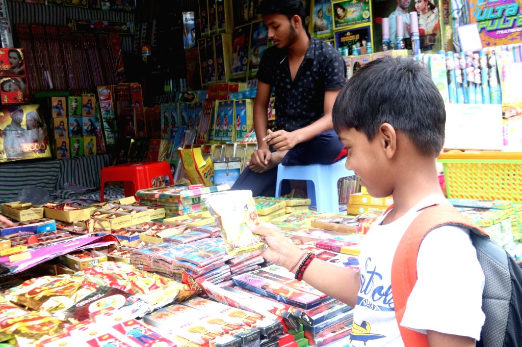 A child checks out a packet of firecrackers during Diwali shopping, at a market in Varanasi on Oct 26, 2019.