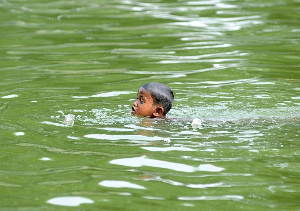 A child cools himself in a pool on a hot day in New Delhi on June 8, 2018.