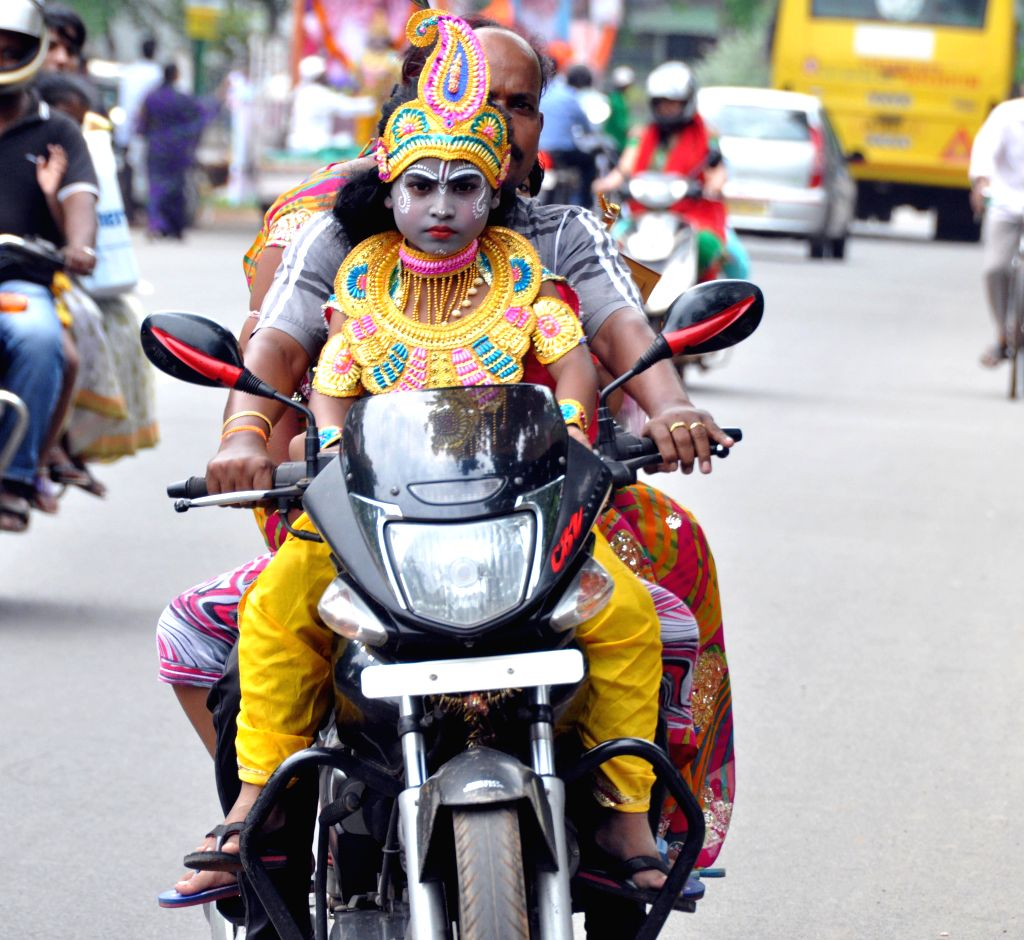 A child disguised as lord Krishna on a bike in Bhubaneswar on Aug 17, 2014. (Photo : Arabinda Mahapatra/IANS)