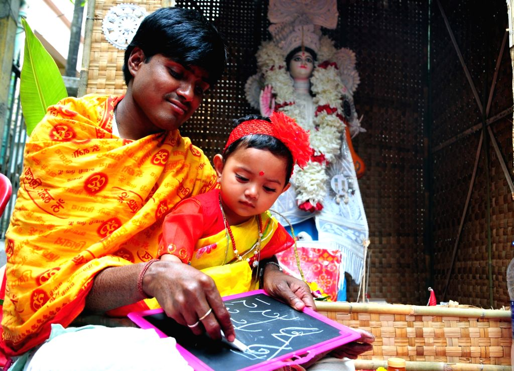 "A child during ""Hate Khori"" - a ceremony where little children are introduced to the first alphabets on Saraswati Puja in Kolkata on Feb 10, 2019."
