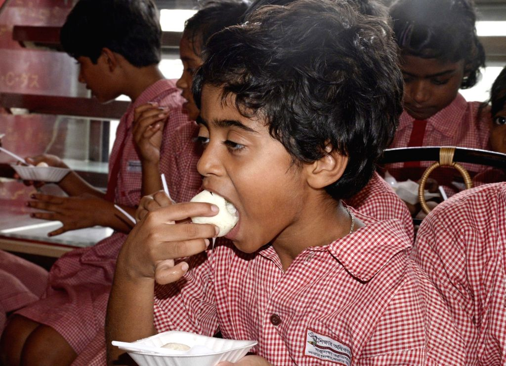 A child enjoys a Rosogolla - an Indian ball-shaped syrupy sweet - during 'Rosogulla Day' being observed across West Bengal on the occasion of Children's Day, in Kolkata on Nov 14, 2019. West ...