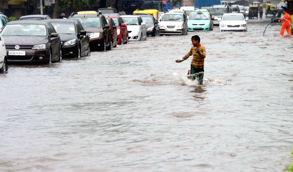 A child enjoys himself on a flooded road of New Delhi as heavy rains lashed national capital on Sept 11, 2014.