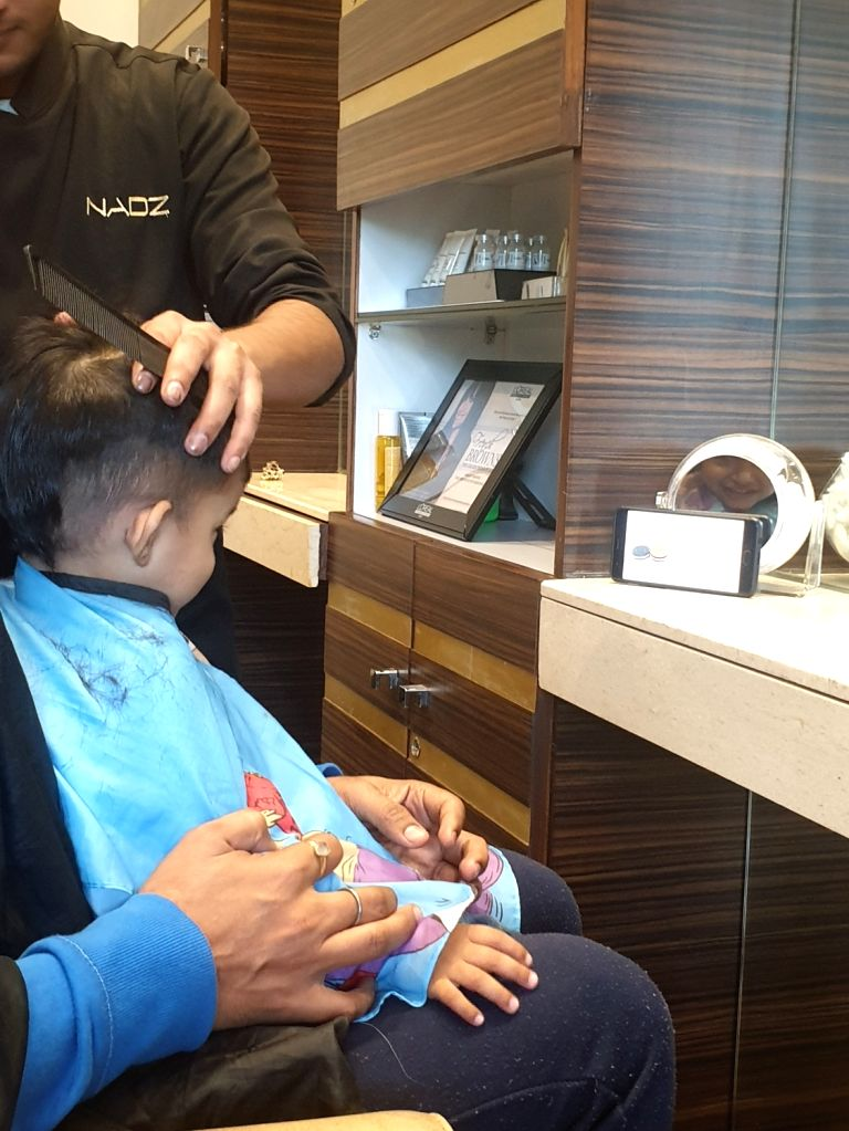 A child glued to a smartphone while getting a haircut.