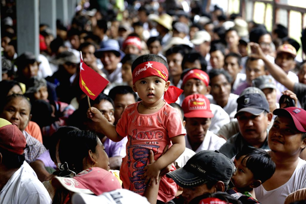 A child holds a flag of National League for Democracy (NLD) as she waits to listen to a speech by Aung San Suu Kyi, leader of Myanmar's NLD during a voter ...