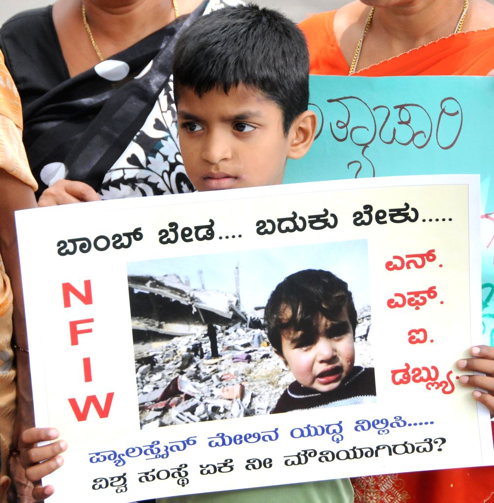 A child holds a placard during a demonstration staged by National Federation of Indian Women against Israeli attacks on Gaza in Bangalore on July 20, 2014.