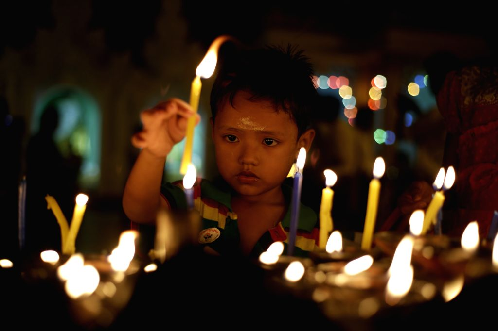A child lights candles on Myanmar's traditional Tazaungdaing Festival at the Shwedagon Pagoda in Yangon, Myanmar, Nov. 26, 2015. The Tazaungdaing Festival, also ...