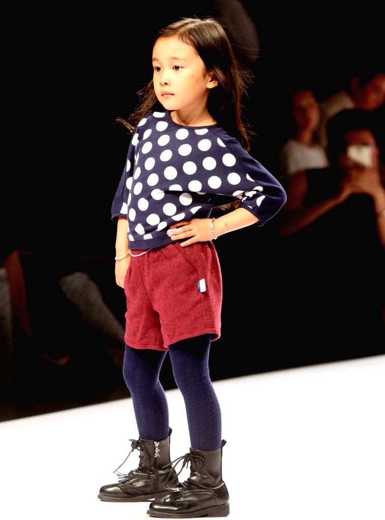 A child model presents a creation during the Shanghai Fashion Week in east China's Shanghai, Oct. 21, 2015.