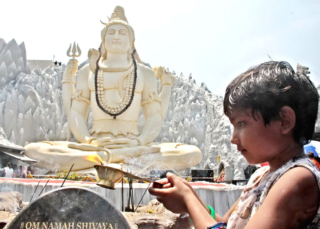 "A child performs an ""Arti"" on Maha Shivratri at Shivoham Shiva Temple, in Bengaluru, on March 4, 2019."