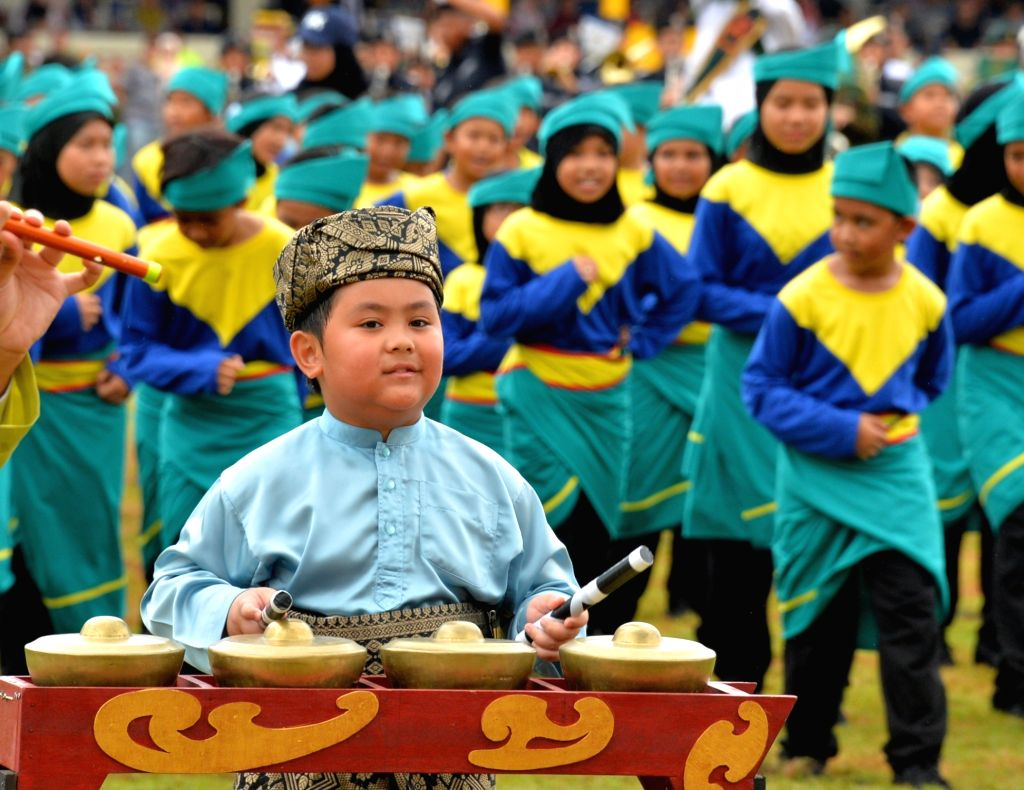 A child plays a traditional musical instrument during the 35th National Day celebration in Bandar Seri Begawan, capital of Brunei, Feb. 23, 2019. Brunei ...