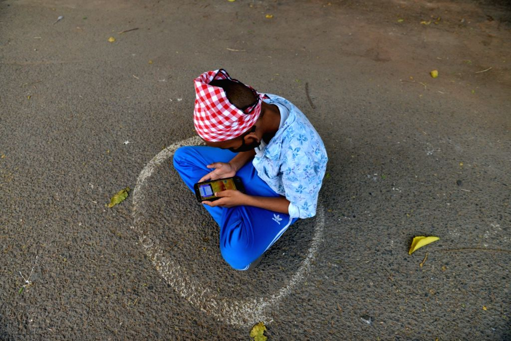 A child sits in a painted circle following social distancing playing a game on mobile as he waits for food distributed by volunteers during the extended nationwide lockdown imposed to mitigate ...